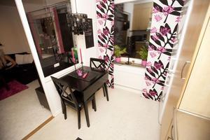 Konsekvent. Carolina Axberg har hållit fast vid sin rockiga rosa och svarta stil i hela ettanm, som är på drygt 30 kvadratmeter. Köksmöblen har hon köpt till fyndpris och målat om själv. Taklampan är köpt på Bauhaus. Lampan i fönstret har hon fått av sin mamma, köpt på Ikea. Fönstret mellan kök och rum ger lägenheten extra ljus. Foto: Anders Forngren
