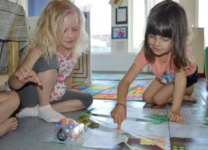 Emilia Wallin och Ester Browall Gustafson hjälps åt för att få roboten att gå som de vill på mattan.