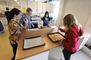 Hemkunskapslärare Anna Karlsson smakar på sockerkakorna som Daniel Henriksson, Elsa Maja Hoyle och Amanda Strömberg bakat.