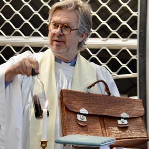 Pastor Jan Bonander tar fram nattvardsflaskan ur sin bandyportfölj inför fjolårets bandygudstjänst på Ljusdals IP.