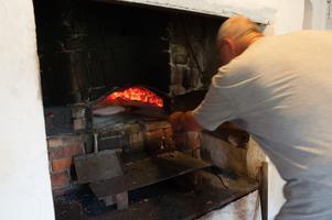 Ton Viesel skjuter in brödet i ugnen. Det krävs minutpassning för att det inte ska bli bränt. – Man måste elda och lägga på mer ved så det inte slocknar säger Ton Viesel. Man måste anpassa tiden till hur varmt det är i ugnen. Om man lagt på mer ved, och om det brinner mycket säger han vidare.