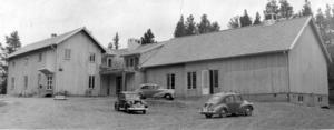 Kluksgården i Alsen, fotograferad 1953. Kanske någon bilintresserad läsare vet vilka märken det är på de fina fordonen som parkerats utanför?