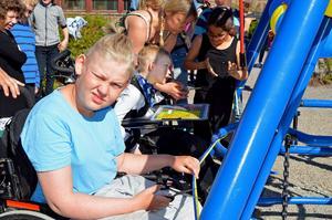 Rasmus Olsson och Melvin Sjöblom klipper bandet och inviger den nya rullstolsgungan vid Jakobsgårdskolan.