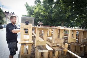 Rasmus Magnusson lastar av bänkarna och borden som är iordninggjorda för gästabudet Svineriet. Foto: Lennye Osbeck