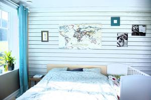 Sovrummet är ljust och vid parets dubbelsäng får sonens spjälsäng bli som en förlängd del.
