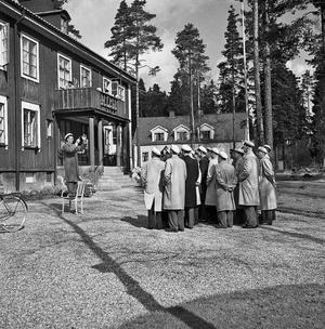 Gammalt foto på manskören som sjunger för de boende på hemmet på valborgsmässoafton.