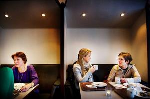 """På Törners konditori i Östersund går det bra att prata i de små båsen. Men visst är det stökigt och lite stressande utanför, tycker Cathrin Skoog där hon sitter och pratar med mamma Ann-Christin. """"Det är svårt att prata med någon på andra sidan bordet"""", förklarar Cathrin. Till vänster i bild Jessica Starck.   Foto: Robert Henriksson"""