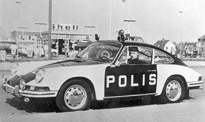 Polisen Jan Eriksson i en Porsche polisbil på Mannatorpsvägen, 1960-talet. Han arbetade vid Länstrafikgruppen. Endast några förare med specialutbildning fick köra bilen. Fotograf: Okänd