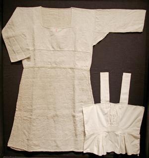 En överdelssärk av tre olika kvalieteter av grovt linne från Jättendal händer bredvid en hängselsärk av bomull med kort nederdel, från Bjuråker.