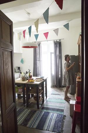 Det gamla huset erbjuder spegeldörrar och höga, vackra fönster. Stora franska antika skåp kompas med skira linnegardiner, svenska trasmattor, en köksö från Ikea. Vimplarna har Lise-Lott sytt själv, klänningen likaså.