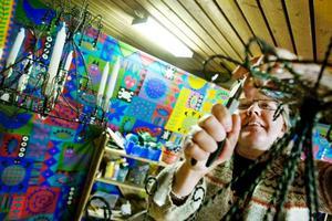 Doris Svensson, Fanbyn, justerar de översta krusidullerna på sin krona. Bakom det färgglada draperiet i bakgrunden döljer sig föreningens materialförråd, en guldgruva för den slöjdintresserade. Foto: Ulrika Andersson
