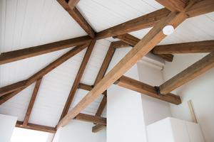 I en av de nyrenoverade lägenheterna har taket lyfts och de gamla träbjälkarna har blivit synliga.