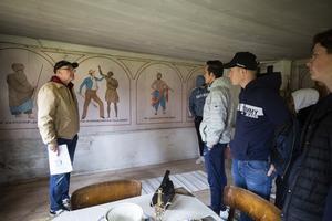 Lars Berglund visar målningarna för elever från Voxnadalens gymnasium.