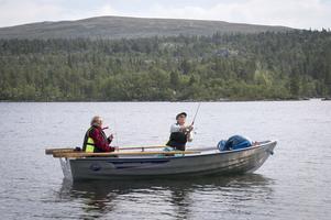 Yvonne Kanebäck från Uppsala och Lotta Vingsle från Umeå fiskar från båt i Hävlingen med Slagufjället i bakgrunden. Foto: Mikael Forslund