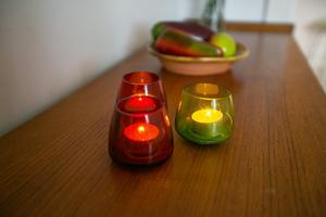 Teak, och ljuslyktor i glas framför frukter av keramik.
