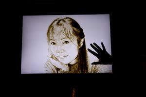 Ofta utgår Chloe från ett foto när hon skapar porträtt i sand, som här sitt eget porträtt.