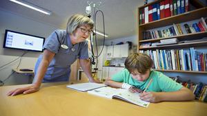 Sjukhusläraren Karin Lönn hjälper tioårige Markus Roth med mattetalen.