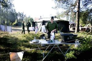 STORKÖK. Roger Larsson diskar medan Lars Lundén och Jörn Eriksen står i bakgrunden. Fältköket serverar Kronans ärtsoppa i 50-litersomgångar, precis som det ska vara. Vissa förhållanden från krigstiden har dock fått ge vika för nutida hälsoregler.