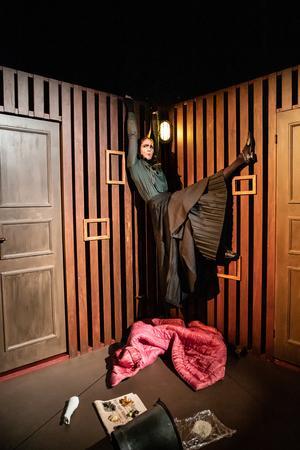 Niki Gunke Stangertz som Gregors mamma i föreställningens finaste stund. Kvinnan är så instängd att hon har andnöd och bokstavligen klättrar på väggarna. Foto: Jenny Baumgartner