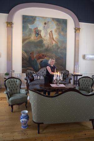 Rådbos har målat väggarna vita och portalen kring altartavlan i ljust lila. Bilden målades av L Kers 1917 – hänförda lärjungar bevittnar hur Jesus stiger upp till himlen. Soffgruppen har Marianne Rådbo hittat i antikboden i Säter.