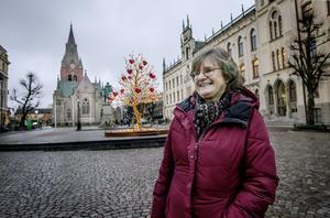Lillvor Ivarsson avfyrar ett leende framför Kärlekens träd på Stortorget. En kontrast till det gråa.