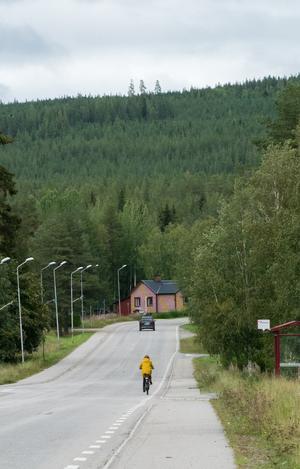 En kvinna i gul kappa cyklar förbi över Ljusnan.