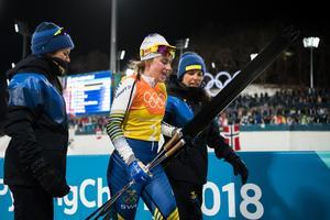 Anna Haag, Ebba Andersson och Charlotte Kalla väntar på att Stina Nilsson ska köra hem OS-silvret. Bild: Joel Marklund/Bildbyrån