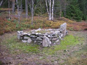 Så här ser den märkliga graven i Vangsta ut i dag.  Före restaureringen bestod  graven av en kringkastad stensamling dold av ett tätt buskage. Magnus Holmqvist ,från länsmuséet, som utförde restaureringen,  upptäckte att det var en omsorgsfullt konstruerad grav med en kallmurad ram av flata stenar och en jordfyllnad i mitten som innehöll själva graven. I hörnen stod uppresta stenar, varav sydstenen, som var högst, stod kvar i orubbat läge. Foto: Lars Högberg