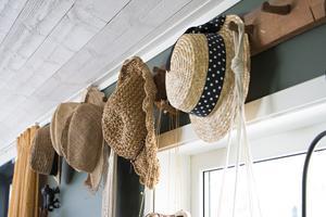 På den gamla knoppbrädan hänger hattar från olika resor som familjen gjort tillsammans.
