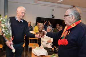 Torbjörn Lindgren fick varm uppskattning av årsmötet för sina mångåriga förtjänstfull insatser för FN-föreningen. Föreningens ordförande Stellan Bäcklund överlämnade en gåva. Foto: Sven Lindblom