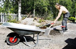 """Micke Jönsson, Östersund, arbetar med att sätta stenar och bygger en stentrapp. """"Jag har ett stillasittande jobb och nu när jag håller på med sådant här arbete på semestern så känns det att man inte är van. Men jag har klarat mig utan skador så här långt """", säger Micke Jönsson.  Foto: Henrik Flygare"""