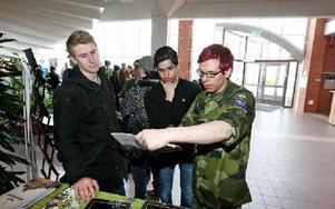 Vid Försvarsmaktens utställningsbord är många intresserade. Jacob Janssen och Rodi Güzel får information av Christian Bower, yrkesinformatör. Många elever har sökt till grundutbildning hos Försvarsmakten.