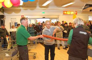 Butikschefen Mattias Svensson och den anställda Gunilla Thor Hell håller i den specialgjorda falukorven då föreningens ordförande Thomas Åhlèn hugger in på korven med en häcksax.