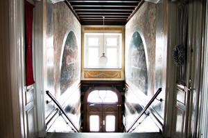 Entrén är minst sagt pampig med väggmålningar och träsnideri i jugendstil.
