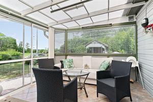 Inglasad veranda som vetter ut mot den stora tomten.