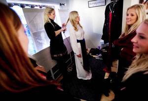 Victoria Rennerståhl gör klar lockarna inför fotografering medan övriga kandidater väntar på sin tur.