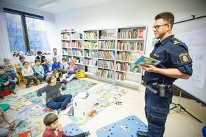 Thomas Nordström, kommunpolis, besökte biblioteket i Krylbo för att läsa en polissaga.