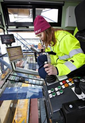 (ettabild?) SE UPP DÄRNERE! Erica Sundell jobbar 25 meter upp i luften i containerterminalen i Gävle hamn. Med vana händer vid spakarna lyfter hon snabbt och lätt containrar som väger över 30 000 kilo.