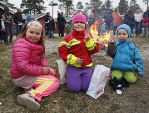 Lova Andersson och Leya och Billy Durhem äter godis som de fiskade upp i fiskdammen.