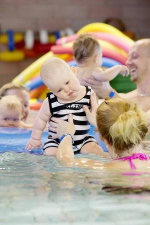 Mira Olsson, 9 månader, får stöd av mamma Sussen på madrassen under sångstunden.