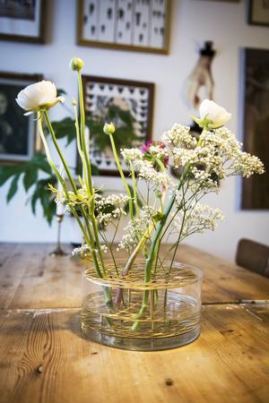 En ny vas med färska blommor pryder bordet i vardagsrummet.