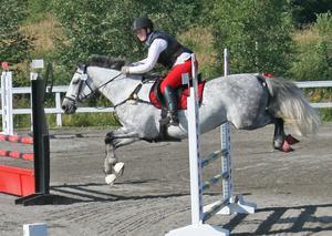 Se så'n stil de har! Här ses Susanne på hästen Mercedes hoppa fint och alldeles tillräckligt högt över hindret under en tävling.