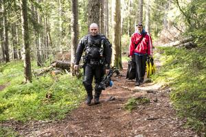En ovanlig syn på skogsstigen till Balestjärn. Martin och Martina Hanell bär med sig utrustning för dykning och undervattensfotografering.