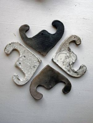Hjärtan, flintstål eller kanske livmödrar? Ida Bratt hittade formen på ett finländskt hus och har bearbetat den i rakubränd lera.