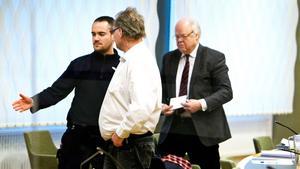 43-åringen under rättegången i Västmanlands tingsrätt 2012-2013. Till vänster en häktesvakt. Till höger hans försvarsadvokat Björn Henriques.