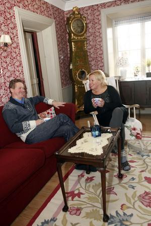 Förmaket. Jan och Leea i favoritrummet. Soffan och mattan är bland de få inredningsdetaljer som inköps nya till hemmet. Det svenska golvuret från 1770 köpte Jan på auktion på 1980-talet.
