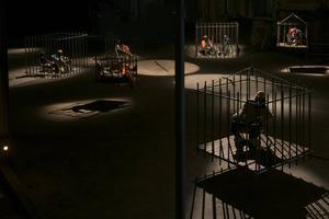 Francesco D'Inceccos verk är en hotfull installation med burar, vapen och gestalter med svarta själar för ansiktet.