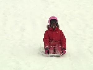 Elisa Muduga testar en platta som man sitter på och åker i snön. Den fick upp ganska bra fart.