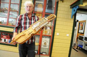 Janne Hansson har snickrat ihop hela 28 nyckelharpor. Här håller han i den senaste som är gjord av gran, äppelträd och älghorn.