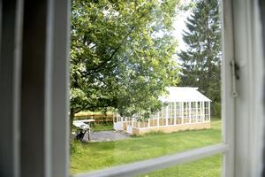 Bakom huset står en vit paviljong, byggd av vita fönster med spröjs.